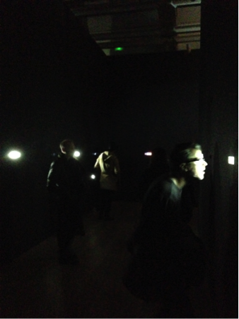Viewers looking at the documents and videos in the walls of Disposition Matrix. Photography: Connor Hamm